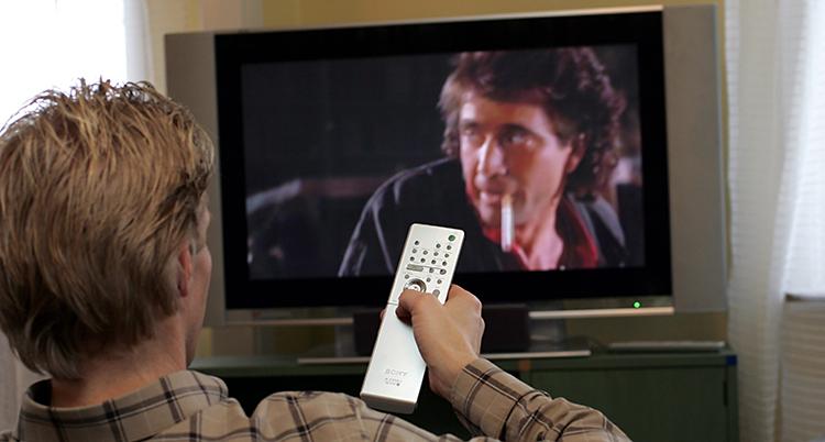 En man sitter i en soffa och tittar på tv. Vi ser mannen bakifrån. Han håller i en fjärrkontroll. På tvn är det en film med en manlig skådespelare.