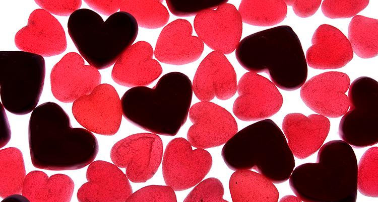 Bilden visar godis som ser ut som hjärtan. De flesta godisarna är röda. Några är svarta. De ligger på en vit bakgrund.