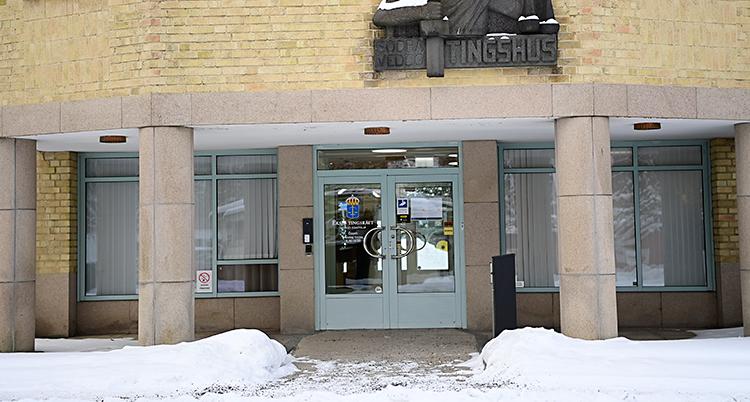 Bilden är tagen utanför domstolen. Det är snö på marken. Vi ser dörrarna in till huset. På en skylt ovanför dörrarna står det Tingshus. Huset är i gult tegel.