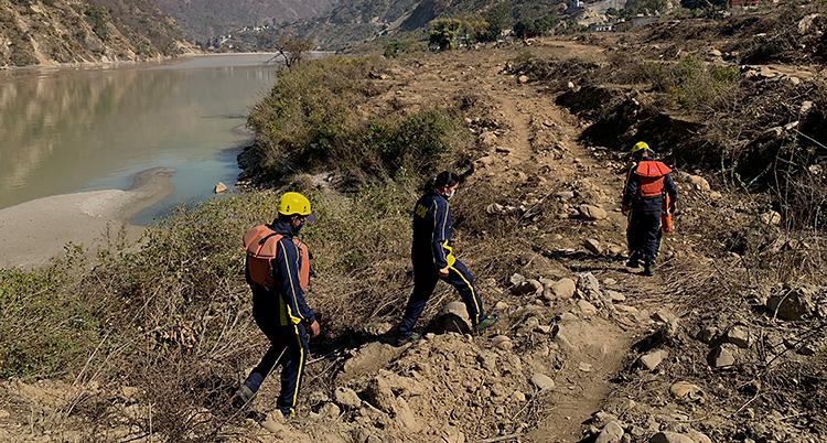 Tre personer går på stranden vid en flod. De letar efter kroppar.