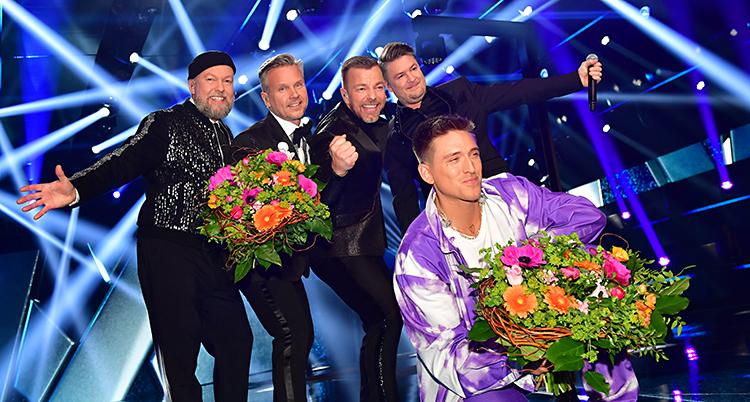 De fyra killarna i Arvingarna står med blommor och är glada. Framför dem sitter Danny Saucedo på huk med blommor. Han är också glad.