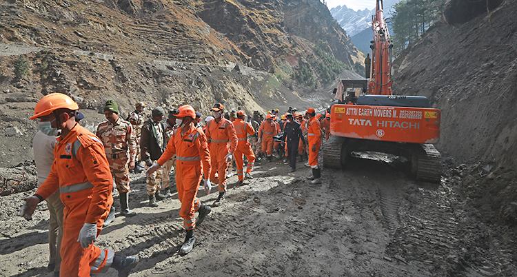Vi ser en dalgång. Det är höga berg runtom. I dalen finns många arbetare med orange kläder och orange hjälmar.