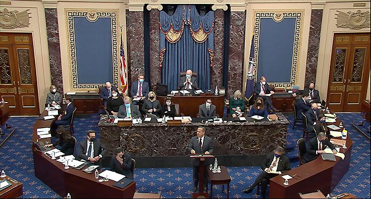 Bilden visar en vacker sal. Där finns skrivbord och bänkar. Flera politiker sitter där.
