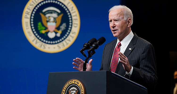 Joe Biden står och pratar i en talarstol. Han har vitt hår. Han har kostym och slips.