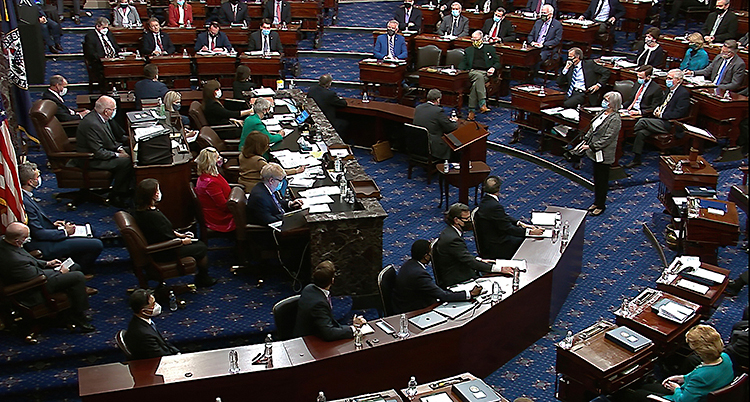 En sal i USAs riksdag. Politiker sitter bakom bänkar.