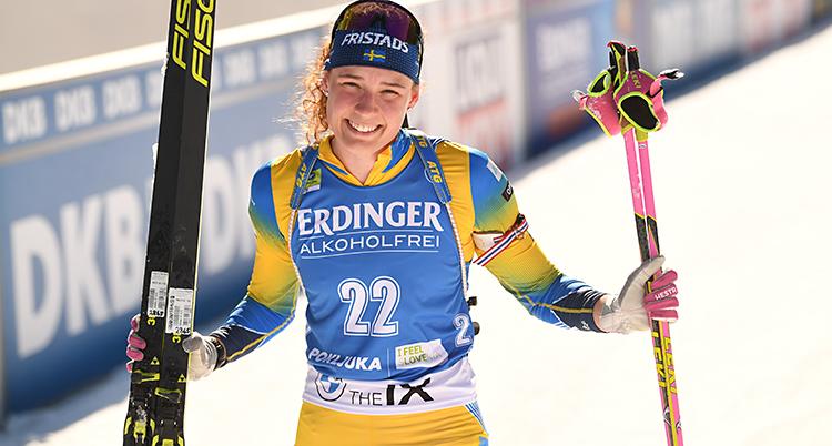 Hanna Öberg ler och tittar in i kameran. Hon håller i sina skidor och sina stavar.