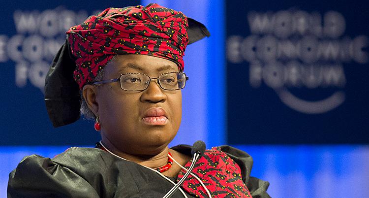 Ngozi Okonjo-Iweala sitter på ett möte. Hon har glasögon. Hon har en dräkt som är röd och svart. Hon har en röd duk snurrad runt huvudet.