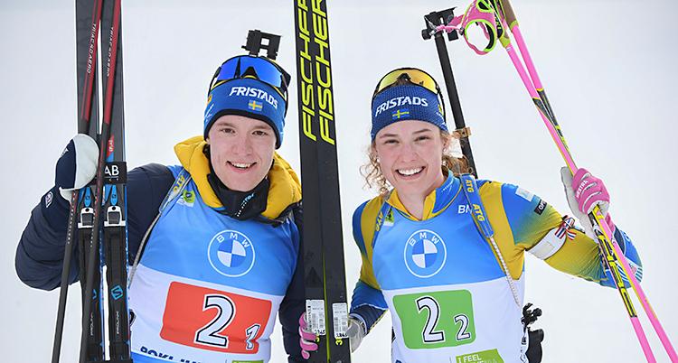 Sebastian och Hanna är glada. De tittar in i kameran. De håller i sina skidor och stavar.