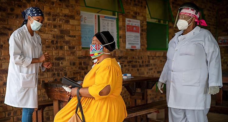 En bild från Sydafrika. Det är tre personer på bilden. Alla har munskydd. I mitten sitter en kvinna i gul klänning. På var sin sida om henne står två andra kvinnor. De har sjukvårdskläder.