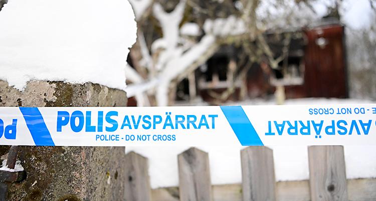 Närmast bilden är det ett staket. Vid staketet har polisen satt upp ett band som är blått och vitt. Där står det Polis avspärrat. Det är snö på marken. Längre bort i bilden syns ett hus som är suddigt.