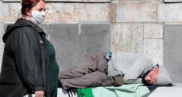 En hemlös man ligger och sover utomhus. En kvinna med munskydd står bredvid.
