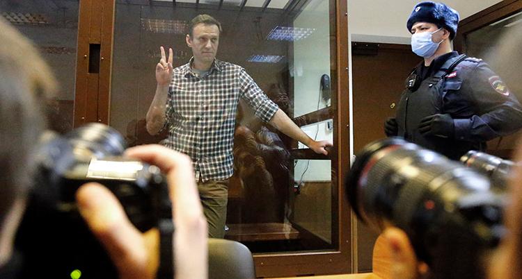 Navalnyj gör segertecknet bakom en glasruta i domstolen. En vakt med vapen står bredvid. Någon tar kort.