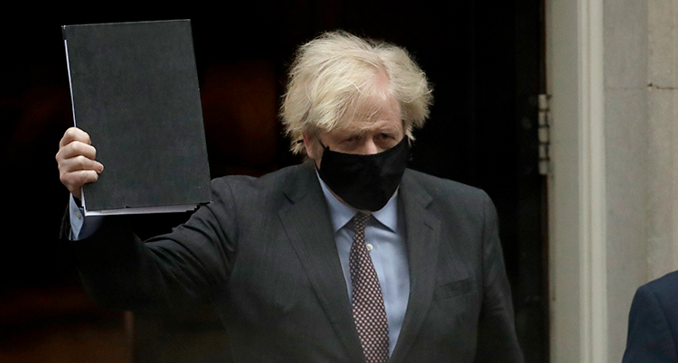 Boris Johnson med vild frisyr och munskydd håller upp en svart pärm.