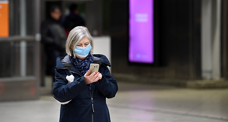 En kvinna står på en perrong. Hon väntar på en tunnelbana. Hon har ett munskydd på sig. Hon håller i en mobiltelefon.