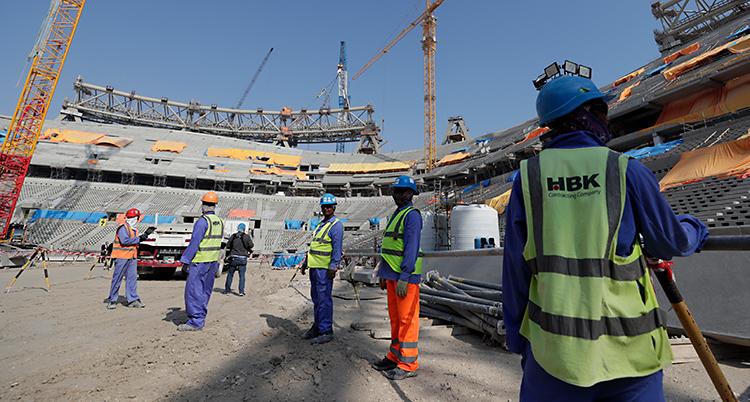 Några arbetare står i mitten av en arena. Arenan är inte klar. Den håller på att byggas.
