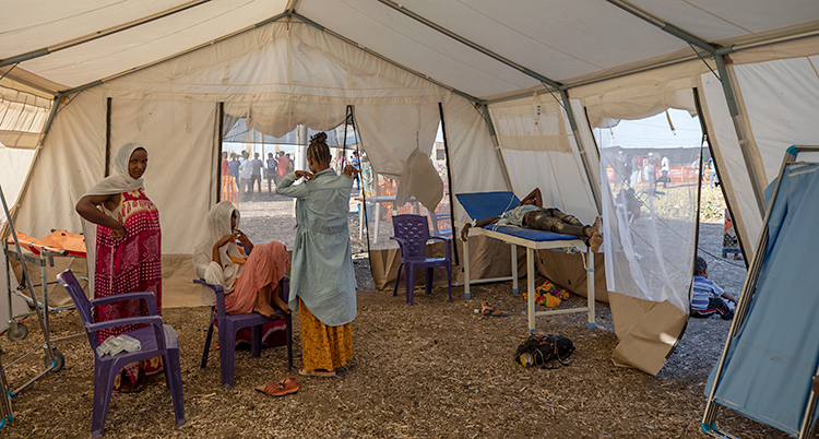 Bilden är tagen i ett stort, vitt tält. Några kvinnor är inne i tältet.