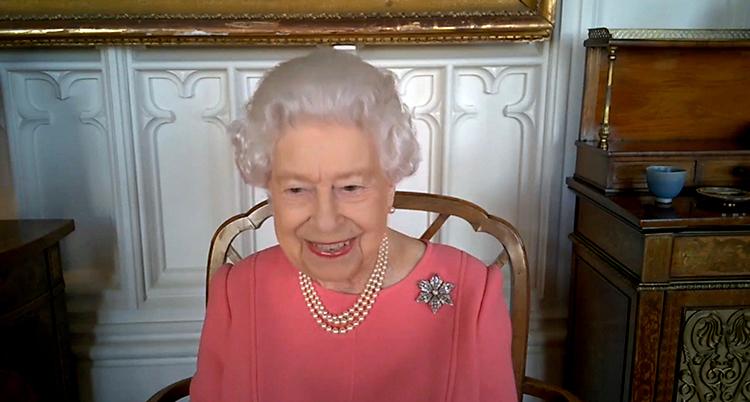 Drottningen sitter på en stol. Hon ler. Hon har grått hår och en rosa dräkt.