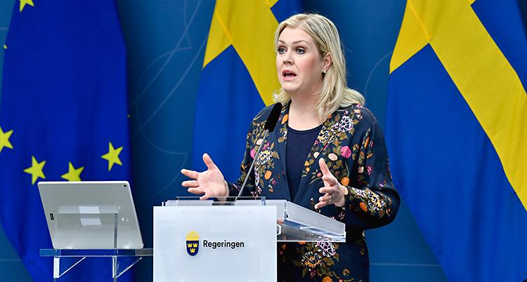 Lena Hallengren pratar för journalister. Hon står vid et litet bord och pratar i en mikrofon. Hon har långt ljust hår. I bakgrunden ser vi Sveriges flagga.