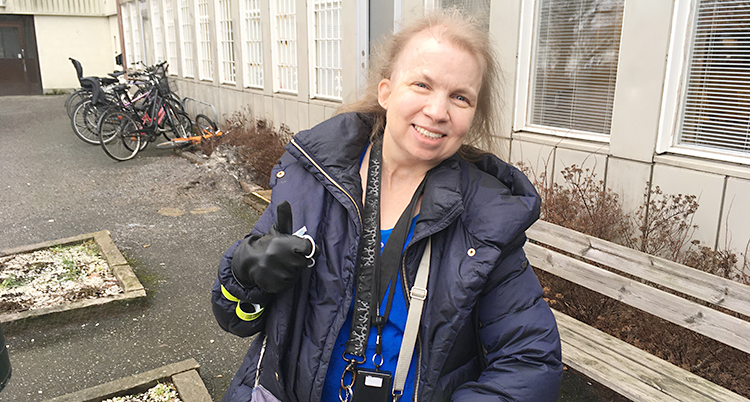 En kvinna står utanför ett hus. Hon ler och tittar mot kameran. Hon gör tummen upp med ena handen. Hon har svarta handskar och en mörkblå jacka.