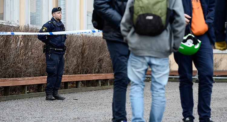 En polis stor bakom ett band där det står polis. Det har hänt ett brott och han vaktar. Några unga står på andra sidan bendet. Man ser deras ryggar