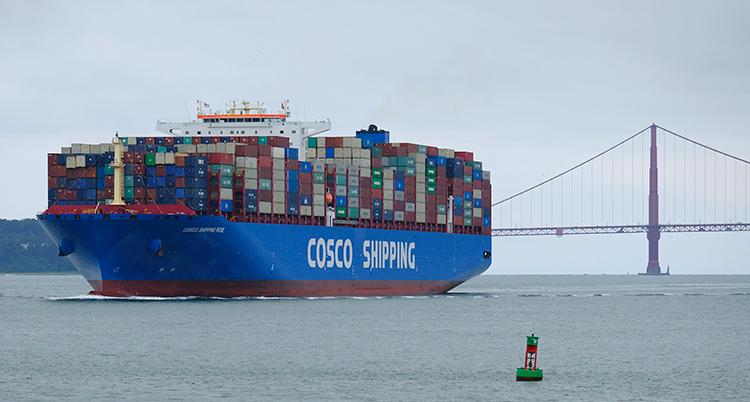 Ett stort blått fartyg är fullastat med containrar och kör på vattnet. Bakom syns en bro.
