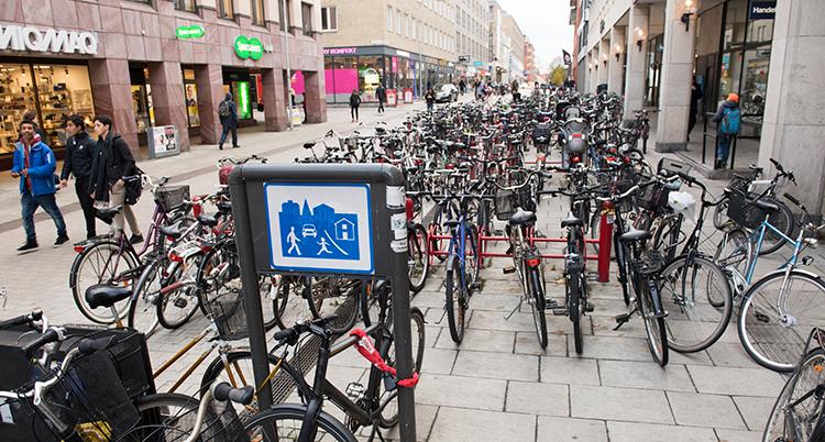 Massor av cyklar står parkerade på en gata.