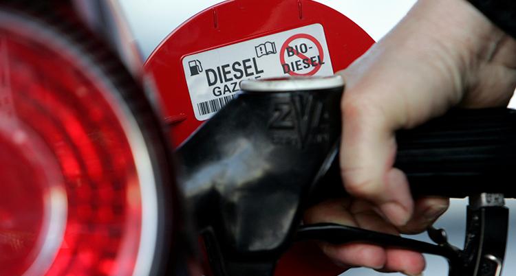 En hand håller i ett munstycke och tankar diesel i tanken på en bil.
