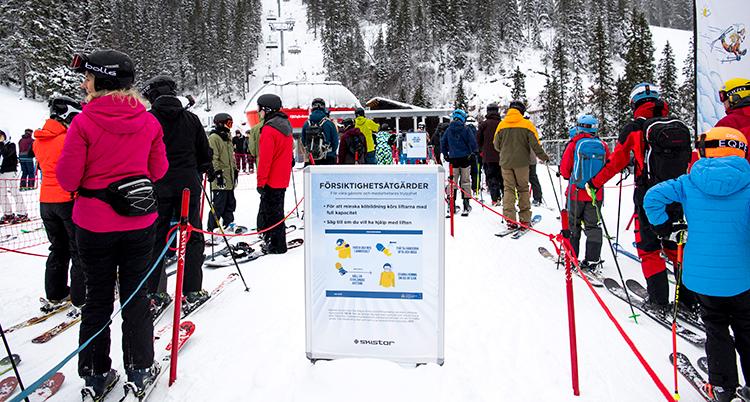 Många människor står i kö till en lift i en skidbacke.