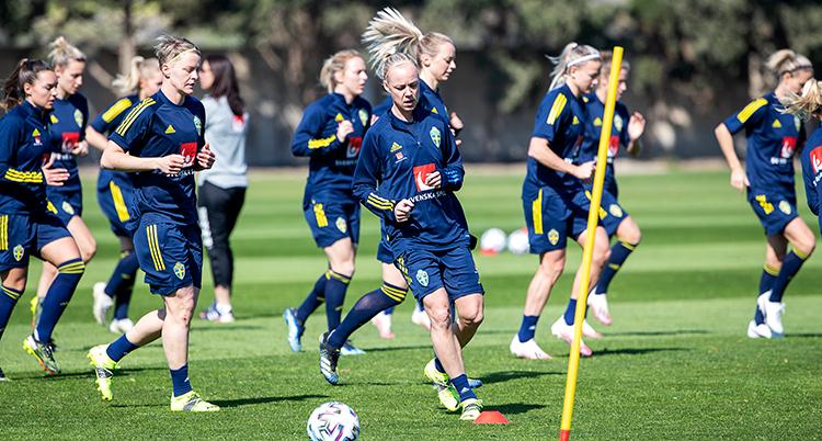 Damer i blå träkter joggar. En spelare längst fram spelar med en boll.