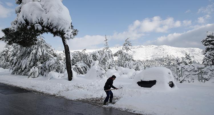 Huset är täckt av snö. Mannen håller i en spade.
