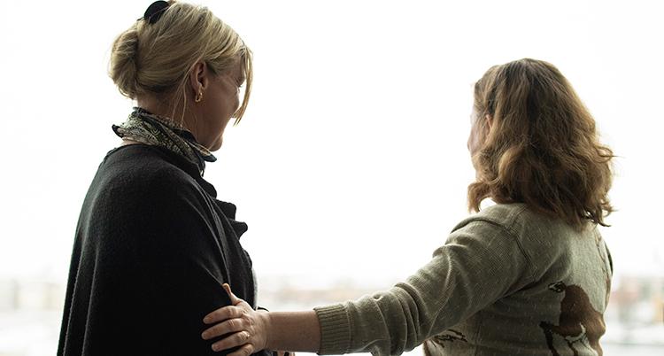 Två kvinnor bredvid varandra. En klappar den andra på armen.