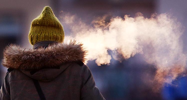 En person står med ryggen mot kamera. Hen har mycket kläder. Rök kommer från munnen. Foot: TT