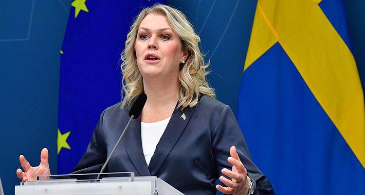 Hon står vid ett podium och pratar i en mikrofon. Hon har ljust hår, gråkavaj och syns mot en blå bakgrund med flaggor.