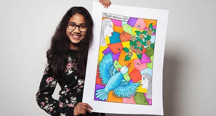 Hon har mörkt hår, glasögon och en blommig överdel. Hon håller i en färgstark affisch.