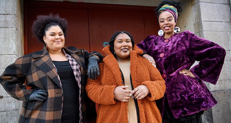 Tre kvinnor står bredvid varandra och lutar sig mot varandra. Alla ler och tittar in i kameran.