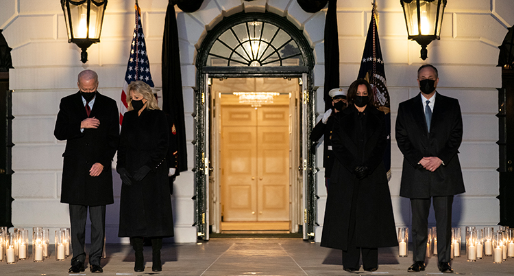 De står framför porten vid Vita huset. Ljuslyktor är tända och står på marken.