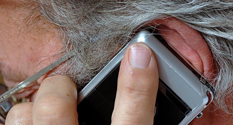 en äldre person pratar i mobilen.