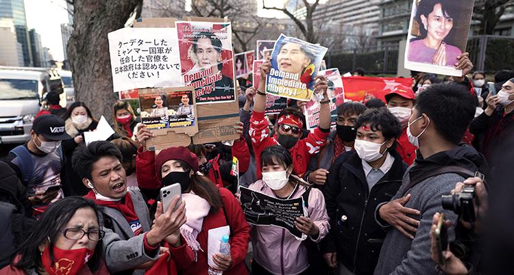 Människor håller upp bilder på Aung San Suu Kyi. Aalla har munskydd.