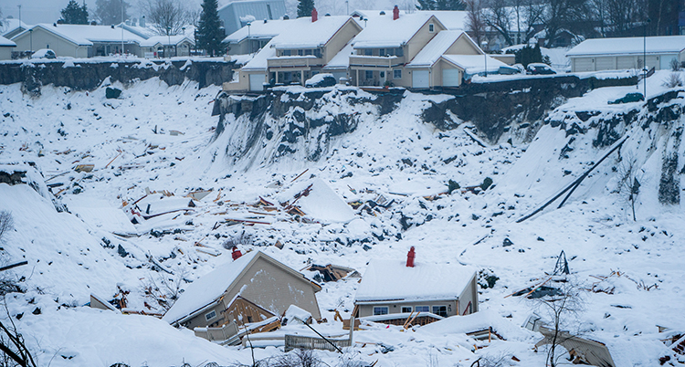 Hus har rasat i ett skred och i bakgrunden syns hus ovanför branten. Det är snöigt.