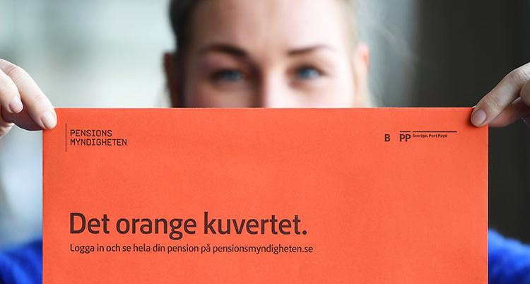 En person håller upp ett orange kuvert. Man ser bara hens ögon och händer.