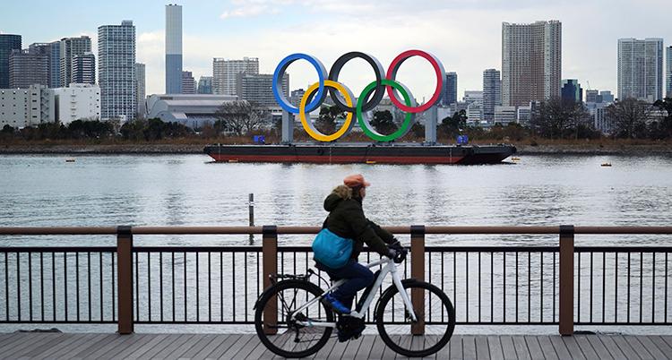 En man cyklar framför en flod. I bakgrunden syns de fem olympiska ringarna.