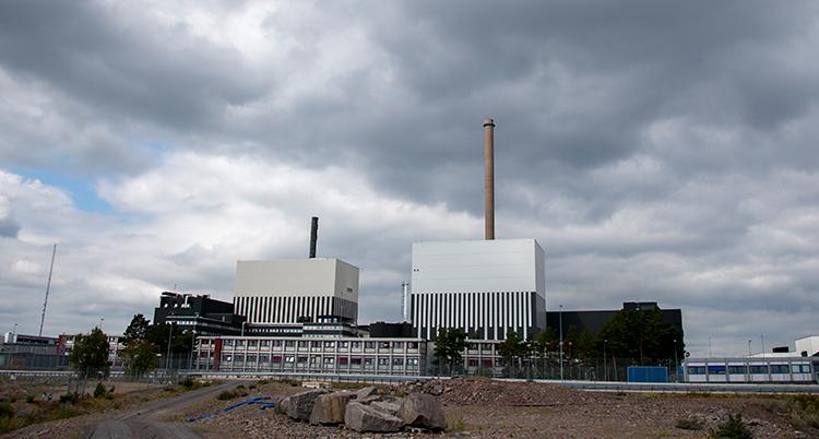 En bild på långt håll av kärnkraftverket. Mörka moln är på himlen.