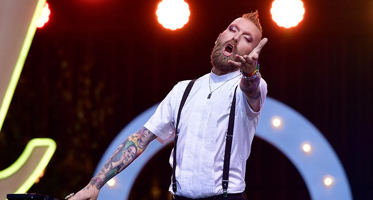 Han sträcker ut vänster arm framför sig, blundar och sjunger. Han har vit kortärmad skjorta och tatueringar som syns på armarna.