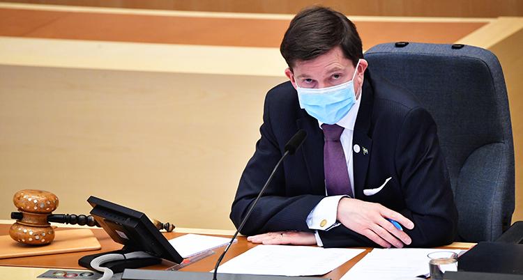 Talmannen sitter bakom sitt bord i riksdagen. Han har munskydd