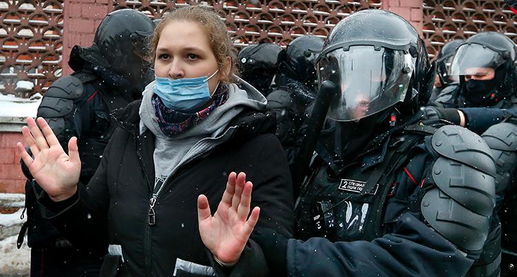 En ung kvinna med munskydd som räcker upp henne. Runt henne är poliser med hjälmar, visir och skydds för bröst och armar. Alla är klädda i svart.