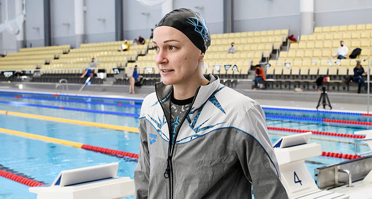 Sjöström går framför en bassäng. Hon har träningsjacka och badmössa. Hon ser allvarlig ut.