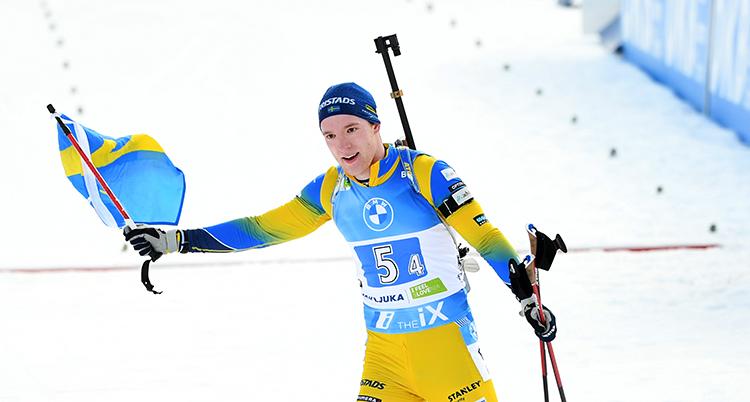 Han sträcket ut armarna och ser glad ut. I ena handen har han en svensk flagga. Han har en gul dräkt och blå mössa.