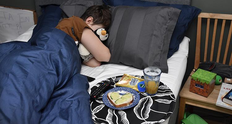 Barnet ligger under täcket i sängen.