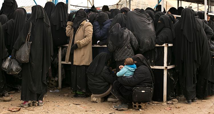 Människor i mörka fotsida kläder står i en kö utomhus. Marken är jordig och torr.