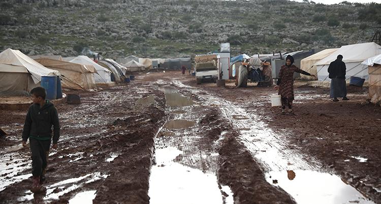 Marken är lerig och har vattenansamlingar. Tält syns i bakgrunden och några människor går i leran.